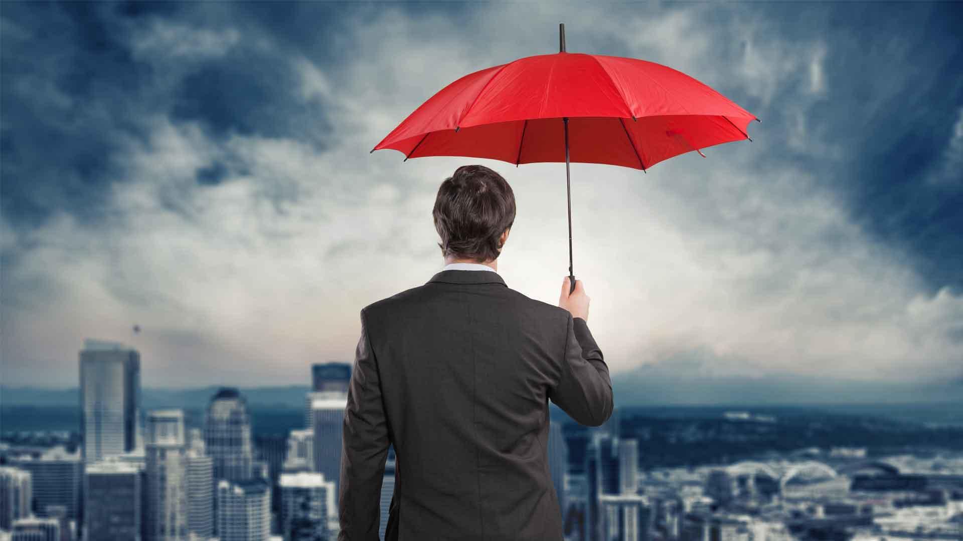 Man standing with umbrella representing umbrella insurance