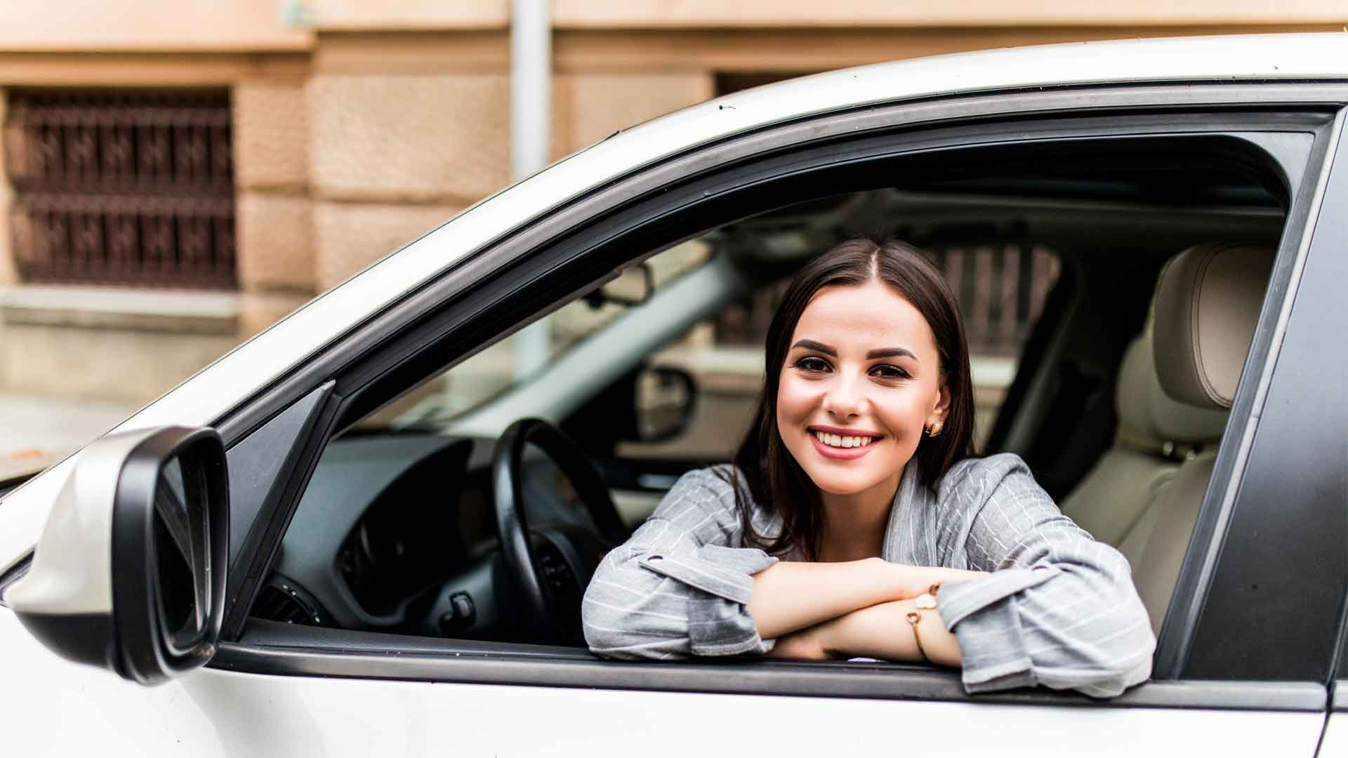 Woman leaning on car protected by an auto insurance policy