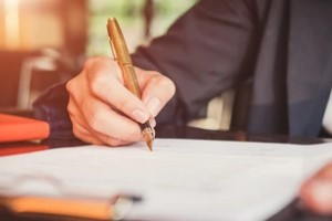 Man Writing with Pen on Paper