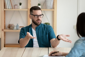 dissatisfied employee wearing glasses arguing with manager