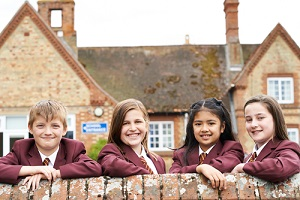portrait of students in uniform outside private school building with insurance for private schools