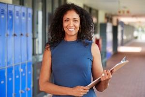 female teacher smiling in school corridor with Educators Legal Liability Insurance
