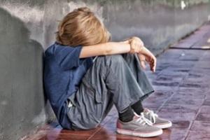 sad child sitting with wall needing abuse and molestation insurance
