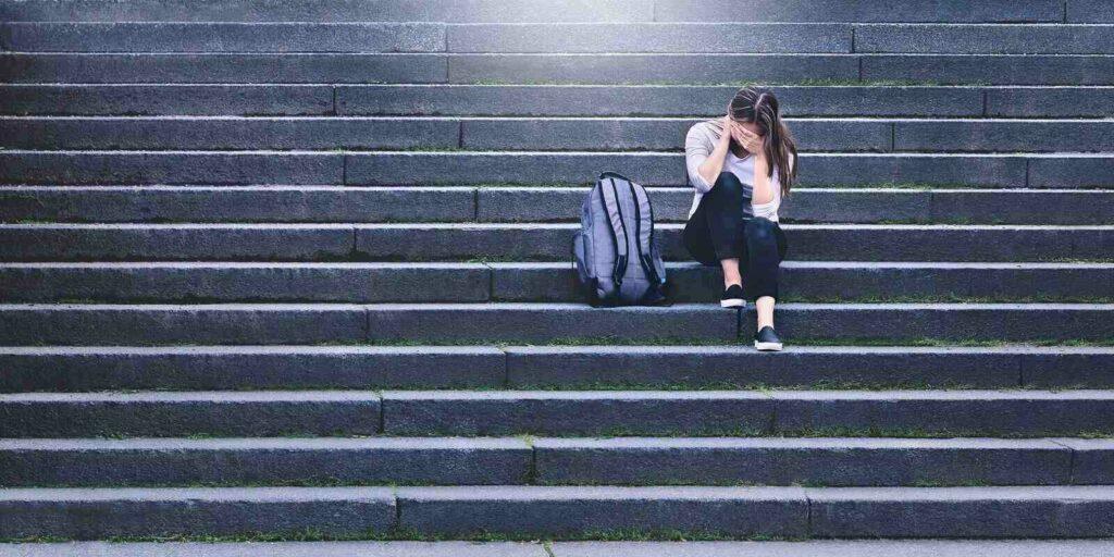 sad teenager crying in school yard