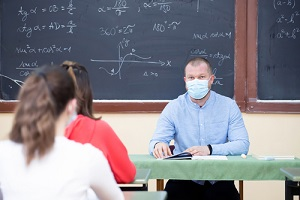 teacher with Educators Legal Liability Insurance and his students wearing protective face mask in the classroom