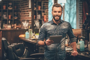 young bearded man looking at camera and holding digital tablet