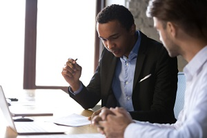 african american businessman reading documents at meeting about third-party liability claims