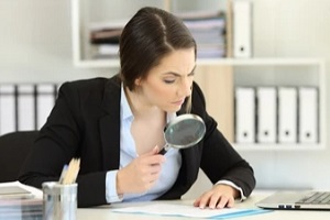 boss checking d&o insurance reports carefully using magnifying glass