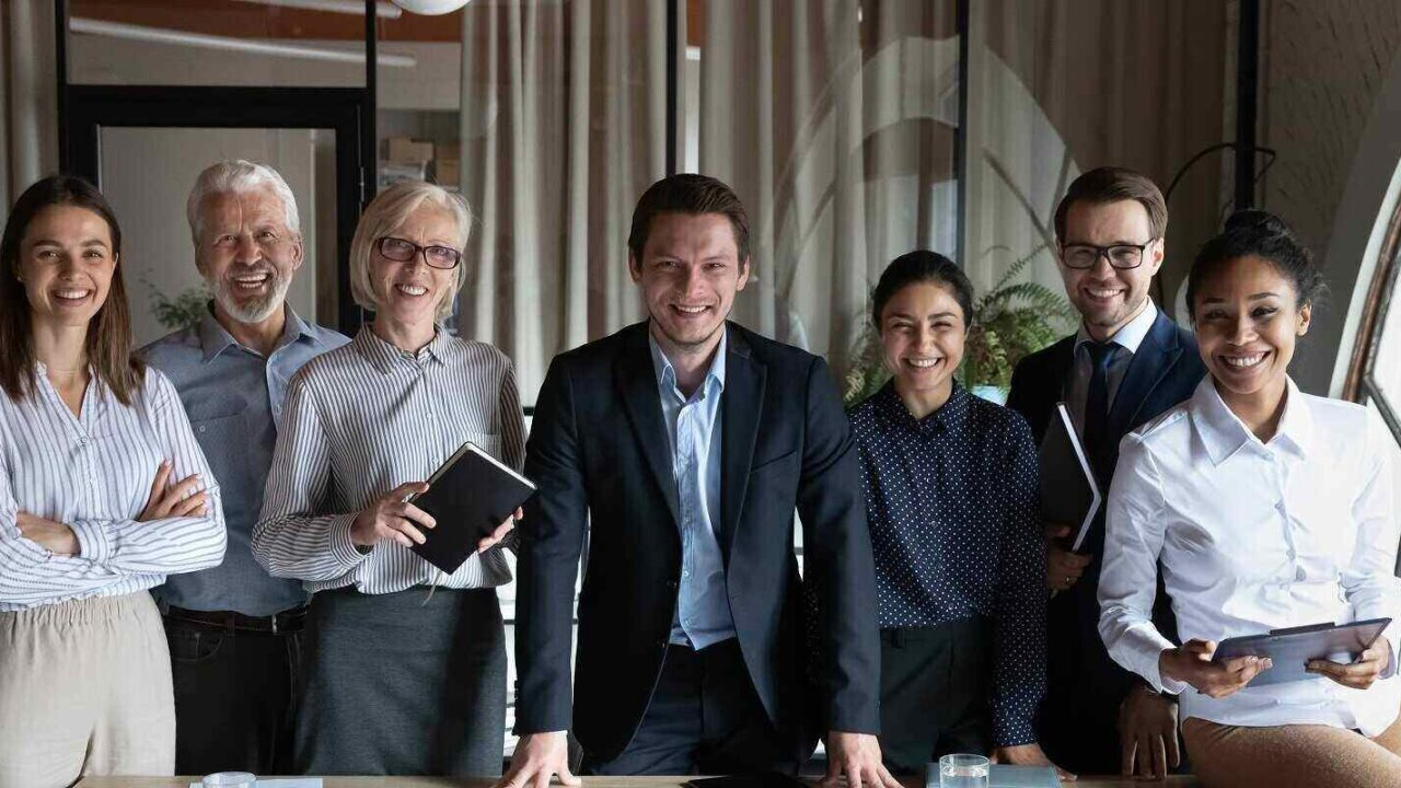 happy multiracial businesspeople stand pose at workplace in modern office